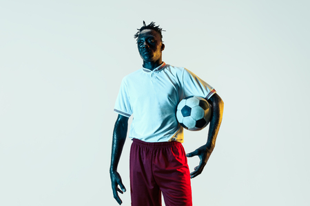 Young african-american male football or soccer player in sportwear and boots standing with the ball in neon light isolated on white background. Concept of healthy lifestyle, professional sport, hobby.