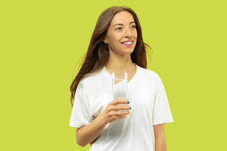 Beautiful young womans half-length portrait isolated on green studio background. Female model looks happy and drinking water. Facial expression, human emotions concept, beauty and healthcare. 免版税图像