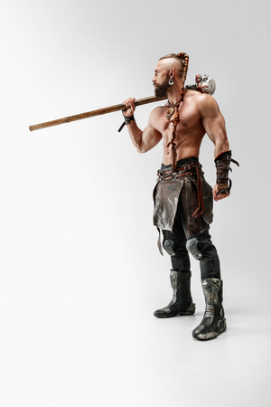Serious long hair and muscular male model in leather vikings costume with the big mace cosplaying isolated on white studio background. Full-length portrait. Fantasy warrior, antique battle concept. Imagens