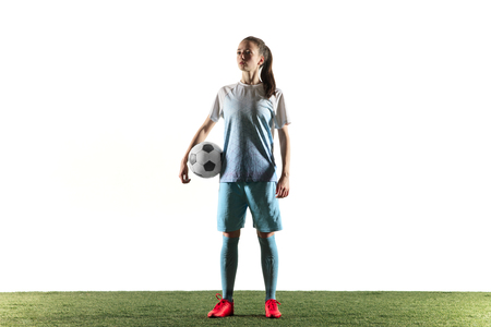 Young female football or soccer player with long hair in sportwear and boots standing with the ball isolated on white background. Concept of healthy lifestyle, professional sport, hobby. Banco de Imagens