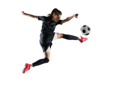 Giovane giocatore di calcio o di calcio femminile con capelli lunghi in abbigliamento sportivo e stivali che danno dei calci alla palla per l'obiettivo nel salto isolato su fondo bianco. Concetto di stile di vita sano, sport professionistico, hobby.
