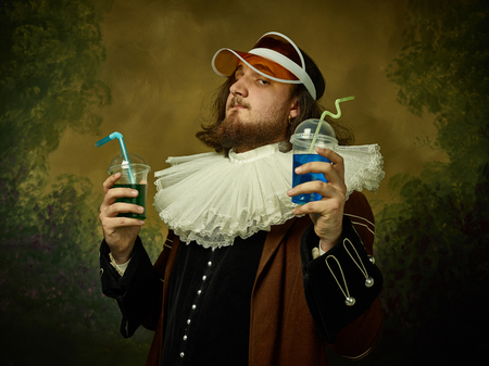 Young man as a medieval knight in red cap on dark studio background. Portrait of male model in retro costume. Holding a drink. Human emotions, comparison of eras and facial expressions concept. 写真素材
