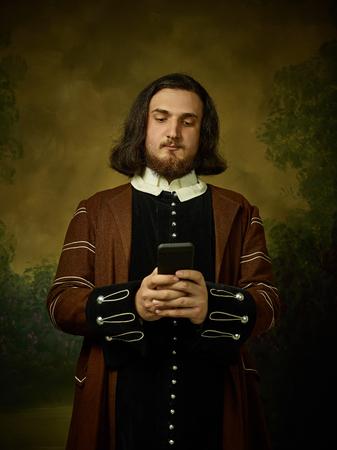 Jonge man als middeleeuwse ridder op donkere studio achtergrond. Portret in low key van mannelijk model in retro kostuum. Selfie maken. Menselijke emoties, vergelijking van tijdperken en gezichtsuitdrukkingen concept. Stockfoto
