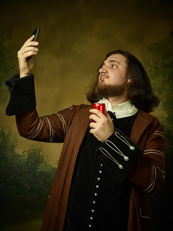 Young man as a medieval knight on dark studio background. Portrait in low key of male model in retro costume. Making selfie. Human emotions, comparison of eras and facial expressions concept. Zdjęcie Seryjne