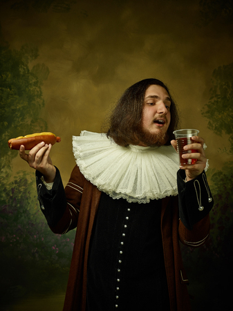 Young man as a medieval knight on dark studio background. Portrait of male model in retro costume. Holding a glass of beer and hot-dog. Human emotions, comparison of eras, facial expressions concept.