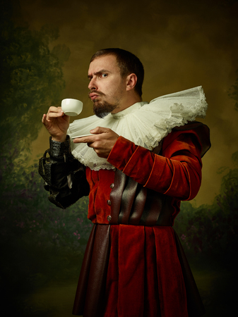 Young man as a medieval knight on dark studio background. Portrait in low key of male model in retro costume. Drinking morning coffee. Human emotions, comparison of eras and facial expressions concept.