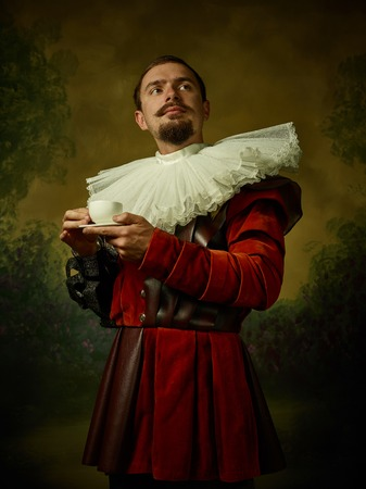 Young man as a medieval knight on dark studio background. Portrait in low key of male model in retro costume. Drinking morning coffee. Human emotions, comparison of eras and facial expressions concept. Foto de archivo