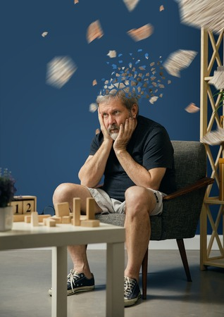 Drown image of losing of mind. Old bearded man with alzheimer desease has problems with his hands motor skills. Illness, memory loss due to dementia, healthcare, neurological disorder, depression. Stock Photo