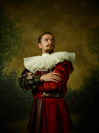 Young man as a medieval knight on dark studio background. Portrait in low key of male model in retro costume. Looks serious. Human emotions, comparison of eras and facial expressions concept.