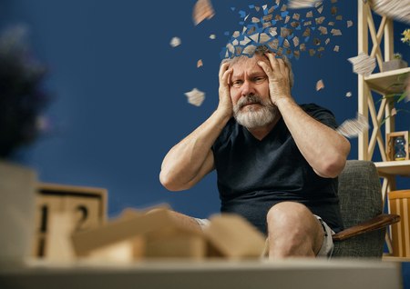 Utopiony obraz utraty rozumu. Stary brodaty mężczyzna z chorobą Alzheimera siedzi i cierpi na ból głowy. Choroba, utrata pamięci z powodu demencji, opieka zdrowotna, zaburzenia neurologiczne, depresja.