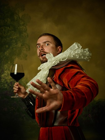 Young man as a medieval knight on dark studio background. Portrait of male model in retro costume. Holding a glass of red wine. Human emotions, comparison of eras, facial expressions concept.