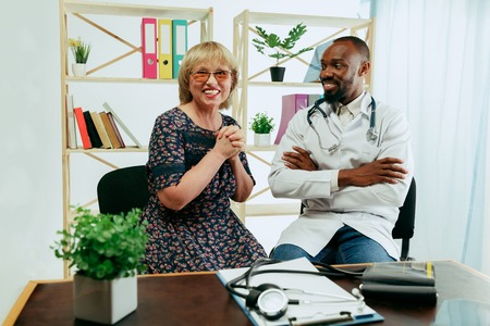 A senior woman visiting a therapist at the clinic for getting consultation and checking her health. Talking to a doctor. Lifestyle portrait at the cabinet. Concept of medicine, healthcare, prevention.