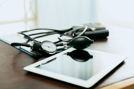 Medical instruments or equpiment for checking blood pressure and a heart beating. Interior of the doctors cabinet or table. Concept of medicine, healthcare and illness or desease prevention.