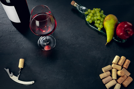 Delicisious and tasty food and drink. A bottle and a glass of red wine with fruits over dark stone background. Top view with copy space to insert your text, image or ad. Grape, apple, pear and corks. Stock Photo - 123125123