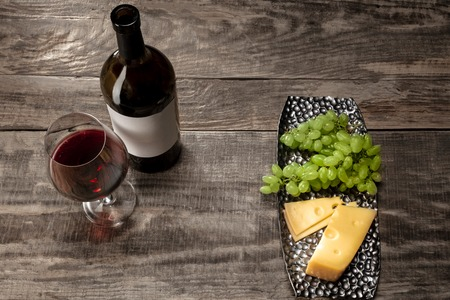 Delicisious and tasty food and drink. A bottle and a glass of red wine with fruits over weathered wooden background. Top view with copy space to insert your text or image for ad. Grape and cheeseplate.