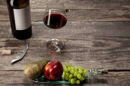 Delicisious and tasty food and drink. A bottle and a glass of red wine with fruits over weathered wooden background. Top view with copy space to insert your ad. Grape, apple, pear and corks.