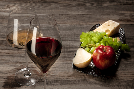 Delicisious and tasty food and drink. A bottle and glasses of red and white wine with fruits over wooden background. Top view with copy space to insert your text or image for ad. Grape and cheeseplate.