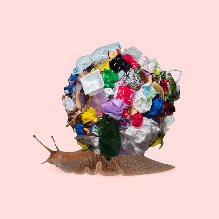 A snail with the big bunch of garbage against trendy coral background. Negative space to insert your text. Modern design. Contemporary art collage. Concept of ecology, environmental problems.