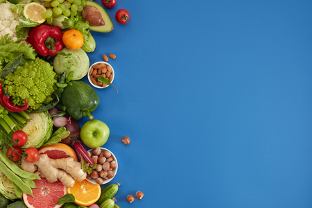 Healthy food dish on blue background. Healthful set including vegetables and fruits. Grape, apple, kiwi, pepper, lime, cabbage, zucchini, grapefruit, ginger, nuts. Proper nutrition or vegetarian menu. Banco de Imagens