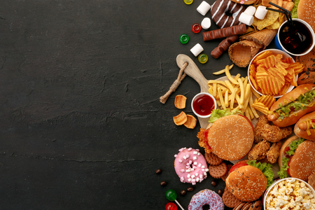 Fast food dish on black stone background. Take away unhealthy set including burgers, sauces, french fries, donuts, cola, sweets, icecream and biscuit. Diet temptation resulting in improper nutrition. Stock fotó