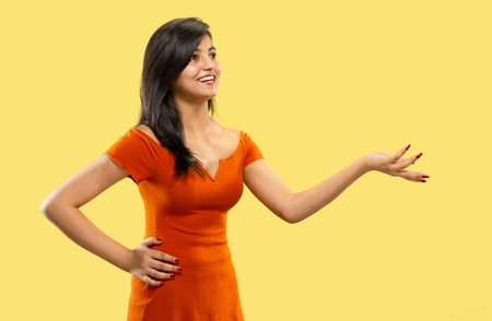 Beautiful female half-length portrait isolated on yellow studio background. Young emotional indian woman in dress pointing and showing. Negative space. Facial expression, human emotions concept.