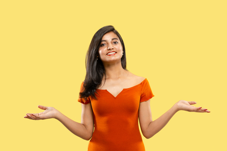 Beautiful female half-length portrait isolated on yellow studio background. Young emotional indian woman in dress pointing and showing. Negative space. Facial expression, human emotions concept. Stok Fotoğraf