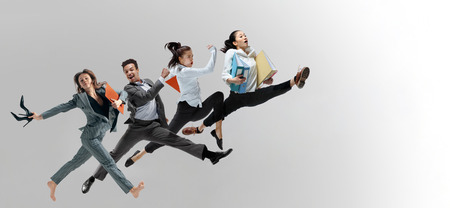 Happy office workers jumping and dancing in casual clothes or suit with folders isolated on studio background. Business, start-up, working open-space, motion and action concept. Creative collage. Stockfoto