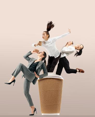 Lets start with aroma coffee. Happy office workers jumping and dancing in casual clothes or suit with hot tasty drinks isolated on studio background. Business, start-up, working open-space concept.