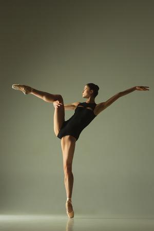 Anmutiger Balletttänzer oder klassischer Ballerinatanz isoliert auf grauem Studio Standard-Bild