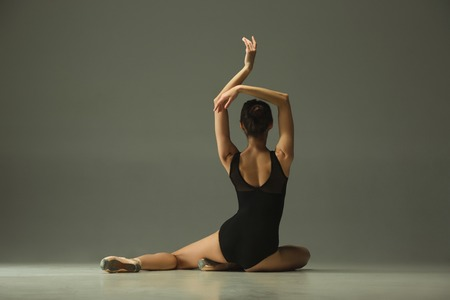 Graceful ballet dancer or classic ballerina dancing isolated on grey studio