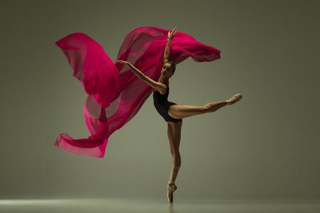 Sierlijke balletdanser of klassieke ballerina dansen geïsoleerd op grijze studio