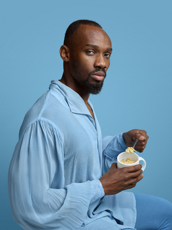 Young man as a medieval grandee on blue background. Portrait of male african-american model in retro shirt. Eating icecream in a cap. Human emotions, comparison of eras, facial expressions concept. Stock Photo