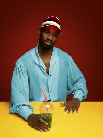 Young man as a medieval grandee or nobleman on red studio background. Holding a glass of drink. Portrait in retro costume and a cap. Human emotions, comparison of eras, facial expressions concept.