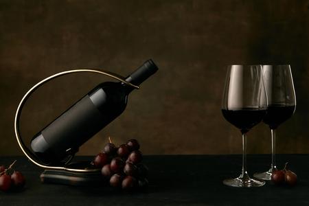 Vista frontal de sabrosas uvas con la botella de vino y vasos sobre fondo oscuro de estudio, copie el espacio para insertar su texto o imagen. Comida y bebida gourmet.