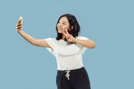 Korean young womans half-length portrait on blue studio background. Female model in white shirt. Making a selfie and smiling. Concept of human emotions, facial expression. Front view.