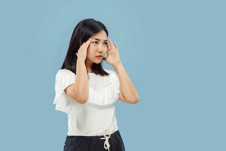 Korean young womans half-length portrait on blue studio background. Female model in white shirt. Thoughtful or suffering of headache. Concept of human emotions, facial expression. Front view.