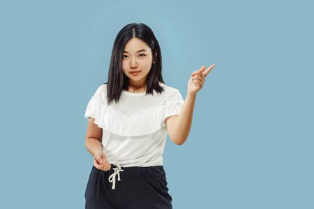 Korean young womans half-length portrait on blue studio background. Female model in white shirt. Showing and pointing something. Concept of human emotions, facial expression. Front view.