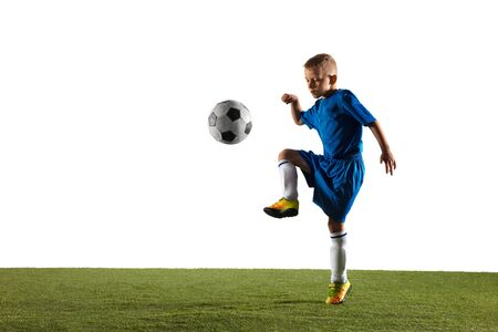 Young boy as a soccer or football player in sportwear making a feint or a kick with the ball for a goal on white studio background. Fit playing boy in action, movement, motion at game. Фото со стока - 124484791