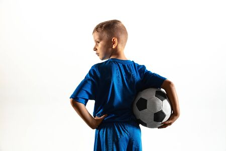 Young boy as a soccer or football player in sportwear standing with the ball like a winner, the best forward or goalkeeper on white background. Fit playing boy in action, movement, motion at game.