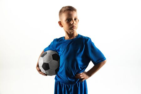 Young boy as a soccer or football player in sportwear standing with the ball like a winner, the best forward or goalkeeper on white background. Fit playing boy in action, movement, motion at game. Stock Photo