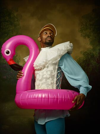 Young man as a medieval grandee or nobleman in a swimring as a pink flamingo on dark studio background. Portrait in retro costume. Human emotions, comparison of eras and facial expressions concept. Stock fotó - 124484967