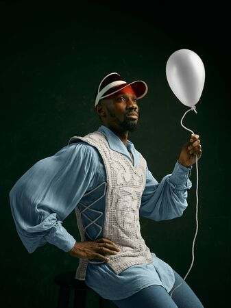 Young man as a medieval grandee or nobleman on dark studio background. Sitting in a cap with the balloon. Portrait in retro costume. Human emotions, comparison of eras and facial expressions concept.