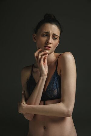 Half-length portrait of young sad woman in underwear on dark studio background. Sadness, depression and addiction. Concept of human emotions, feminism, womans problems and rights, mental health. Standard-Bild - 124485003