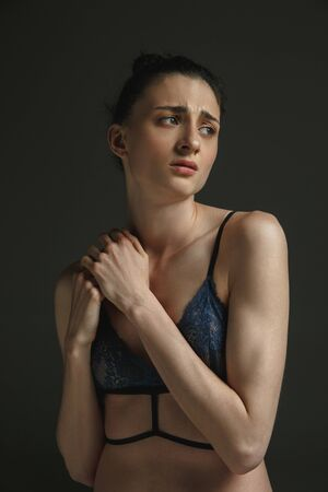 Half-length portrait of young sad woman in underwear on dark studio background. Sadness, depression and addiction. Concept of human emotions, feminism, womans problems and rights, mental health. Standard-Bild - 124485004