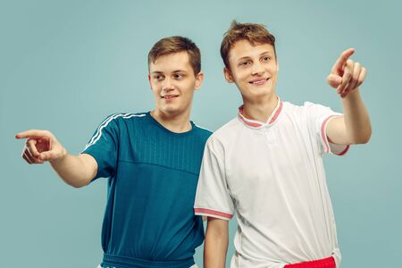 Two young men standing in sportwear isolated on blue studio background. Fans of sport, football or soccer club or team. Friends half-length portrait. Concept of human emotions, facial expression. Stock Photo
