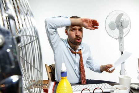 The true hell is here. Young man suffering from the heat in the office. Fans do not help, its like sahara in the centre of the city. Concept of office workers troubles, business, problems and stress.