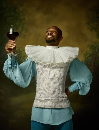 Young man as a medieval grandee or nobleman on dark studio background. Holding a glass of red wine. Portrait in retro costume. Human emotions, comparison of eras and facial expressions concept.