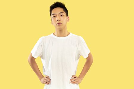 Portrait demi-longueur du jeune homme coréen sur fond de studio jaune. Modèle masculin en chemise blanche. Debout et regardant. Concept d'émotions humaines, expression faciale. Vue de face. Couleurs tendance.