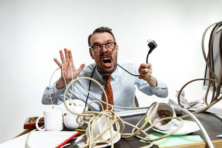 Completely confused. There are a lot of wires in the workplace and man is constantly tangled in them. Its literally blocking him. Concept of office workers troubles, business, problems and stress.
