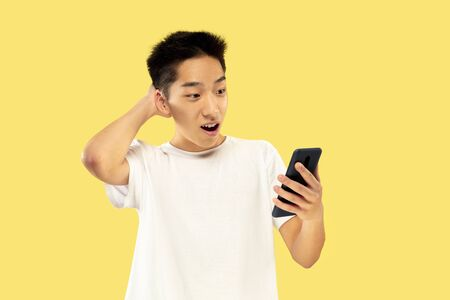 Korean young mans half-length portrait on yellow studio background. Male model in white shirt. Using smartphone for betting, news reading or talking. Concept of human emotions, facial expression. Stok Fotoğraf - 124592405
